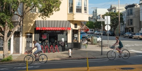 Bicyclists in a bike lane in front of a cafe on Arguello in the Inner Richmond