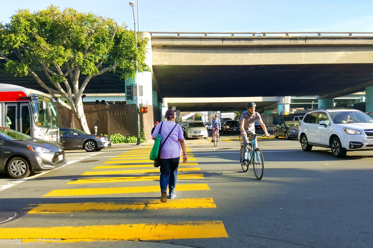 A freeway ramp intersection with cars, people walking, and people biking