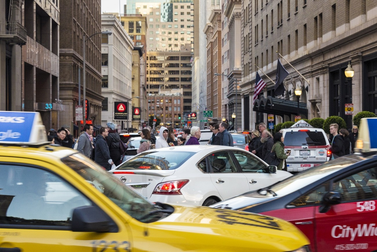 Taxis, an Uber, other cars, and people walking in congested downtown San Francisco