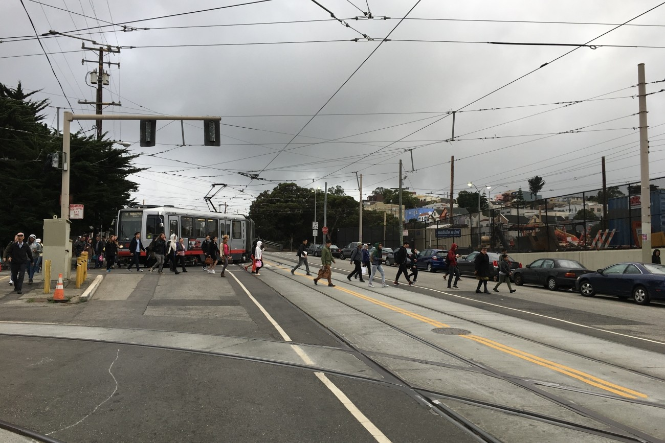 People crossing San Jose Avenue after exiting the Muni light rail.