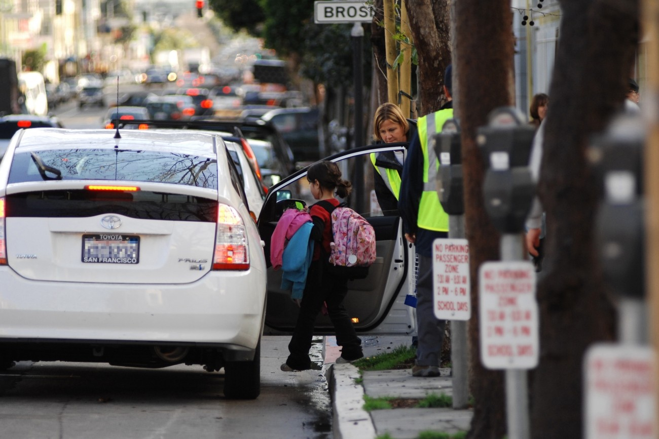 A child getting into a Prius with help from a school aide