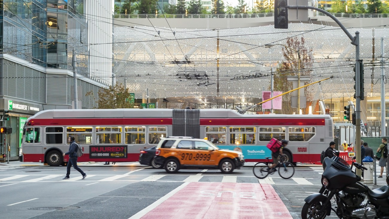 A view of the Salesforce Transit Center, a red transit-only lane, and a bus