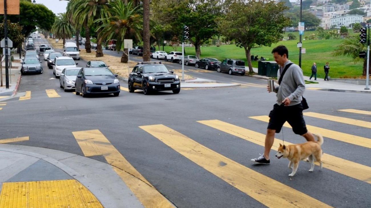 A pedestrian crossing a crosswalk near Dolores Park