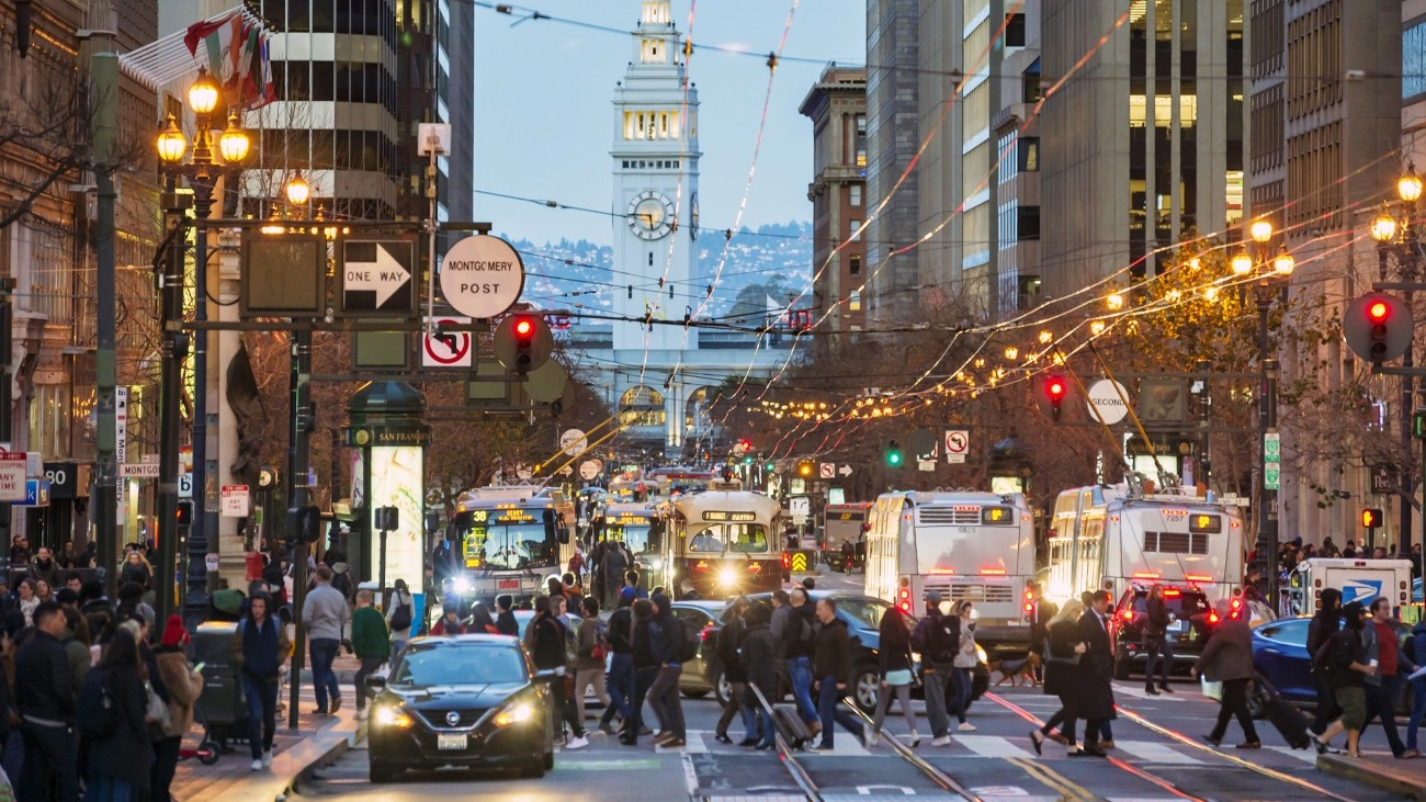 An image of buses and people walking on Market Street in the early evening