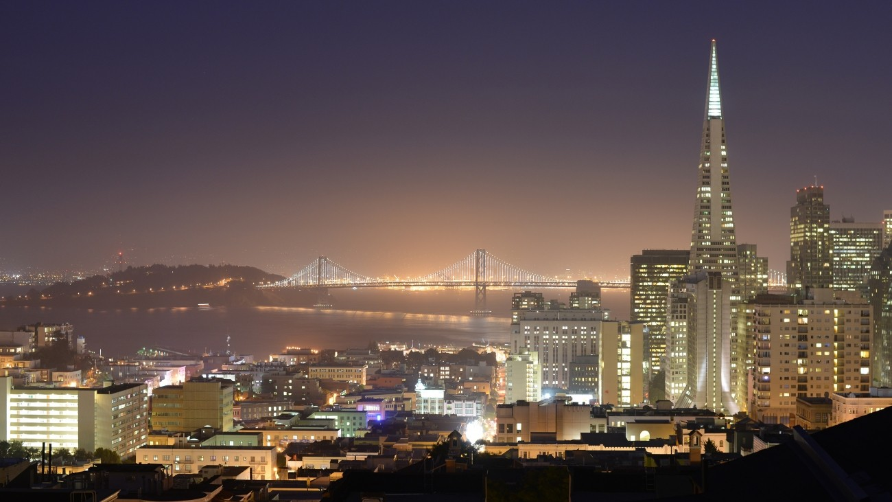 A nighttime view of the Bay including the Bay Bridge and Transamerica building