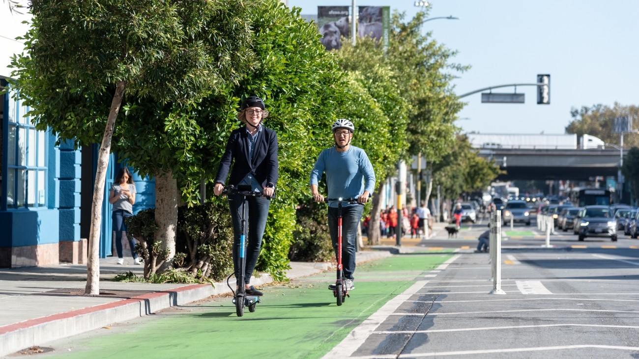 People on scooters in a bike lane
