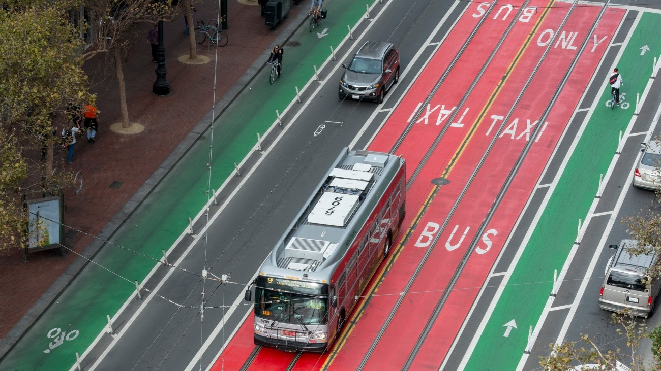 A bus in a red bus-only lane on Market Street, surrounded by green bike lanes.
