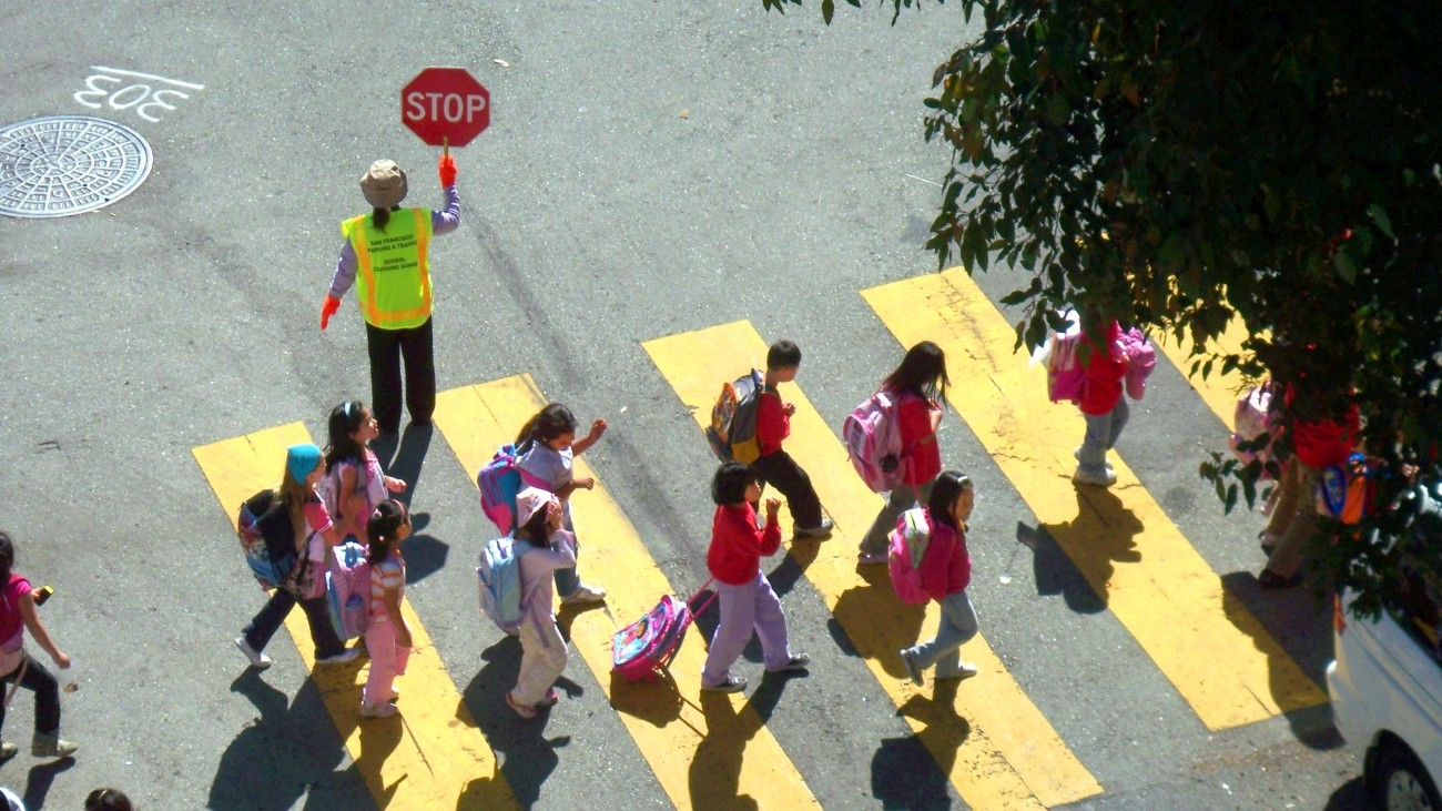 Kids crossing the street in a yellow crosswalk with a crossing guard