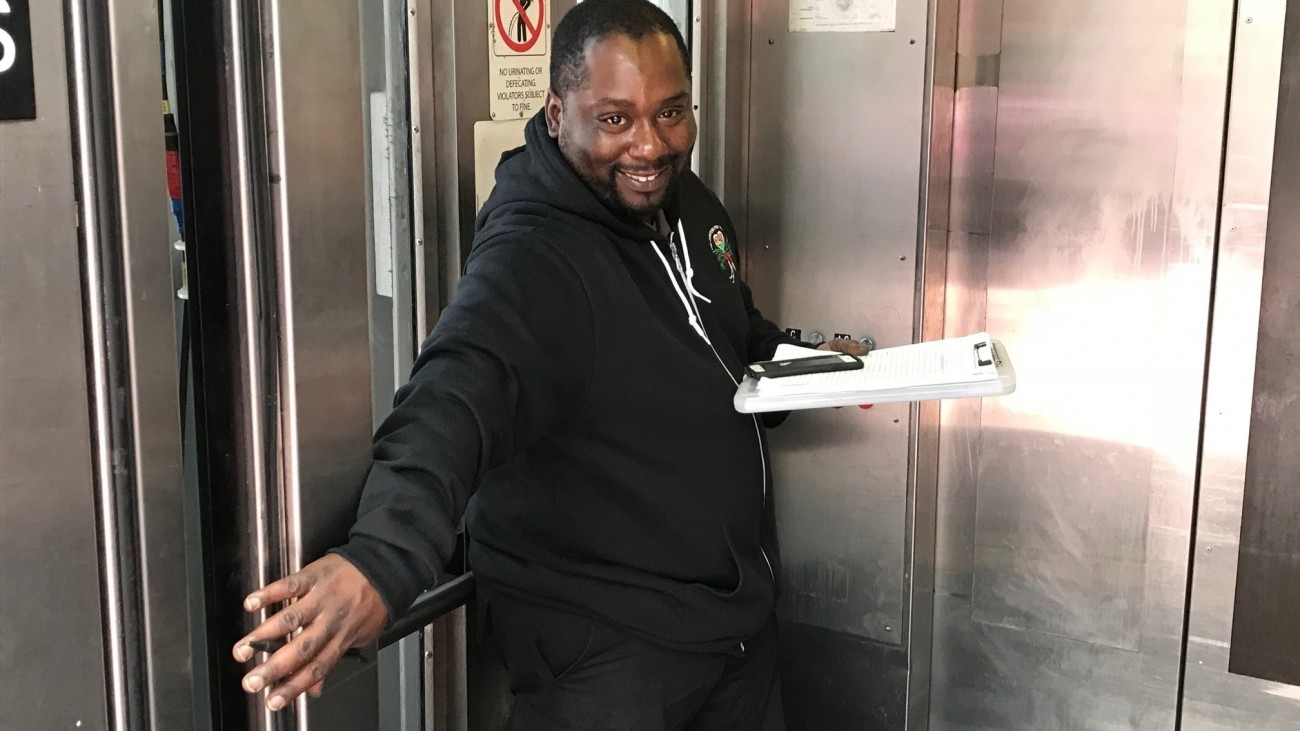 An elevator attendant in an elevator opening the door