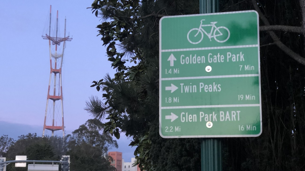 A bike wayfinding sign that gives directions to Golden Gate Park, Twin Peaks, and Glen Park BART