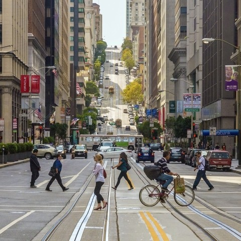 A photo of people walking and biking on Market Street, with a bus and cars in the background