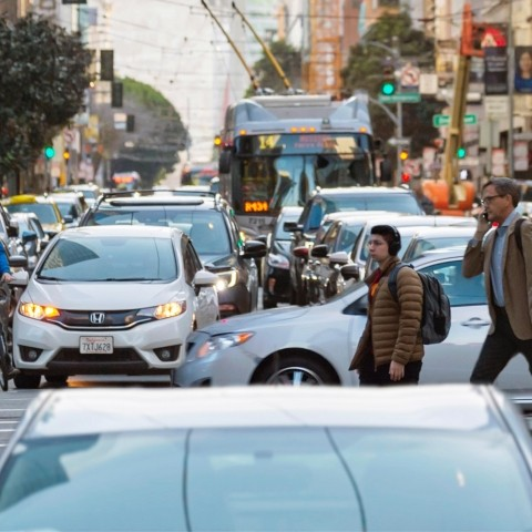 People cross crowded Mission Street as a bus waits in traffic