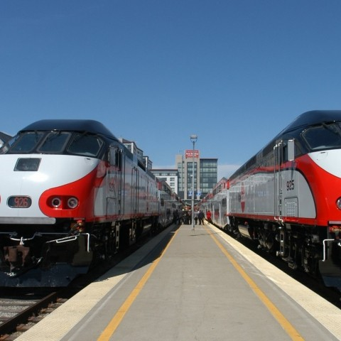 two caltrain trains waiting at the platform